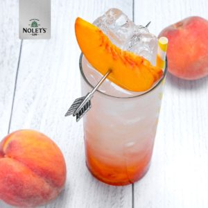 Glass of NOLET'S Peach Lemonade cocktail with 2 peaches